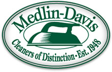 Medlin Davis Cleaners Logo - Oval with 2 line green stroke holding green serif type and hand iron